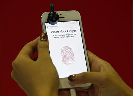 A promoter demonstrates the fingerprint scanner feature of the newly launched Apple iPhone 5S in Singapore