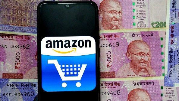 In this photo illustration an Amazon logo seen displayed on a smartphone with the Indian Currency Note One Hundred and Two thousand on the background.