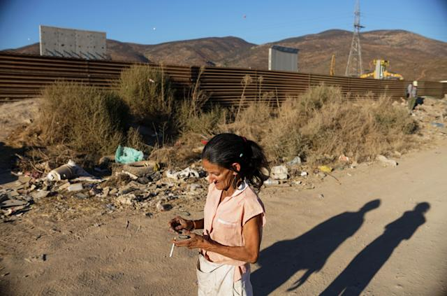 <p>A woman walks past prototype sections of a border wall between Mexico and the United States under construction on October 5, 2017 in Tijuana, Mexico. (Photo: Sandy Huffaker/Getty Images) </p>