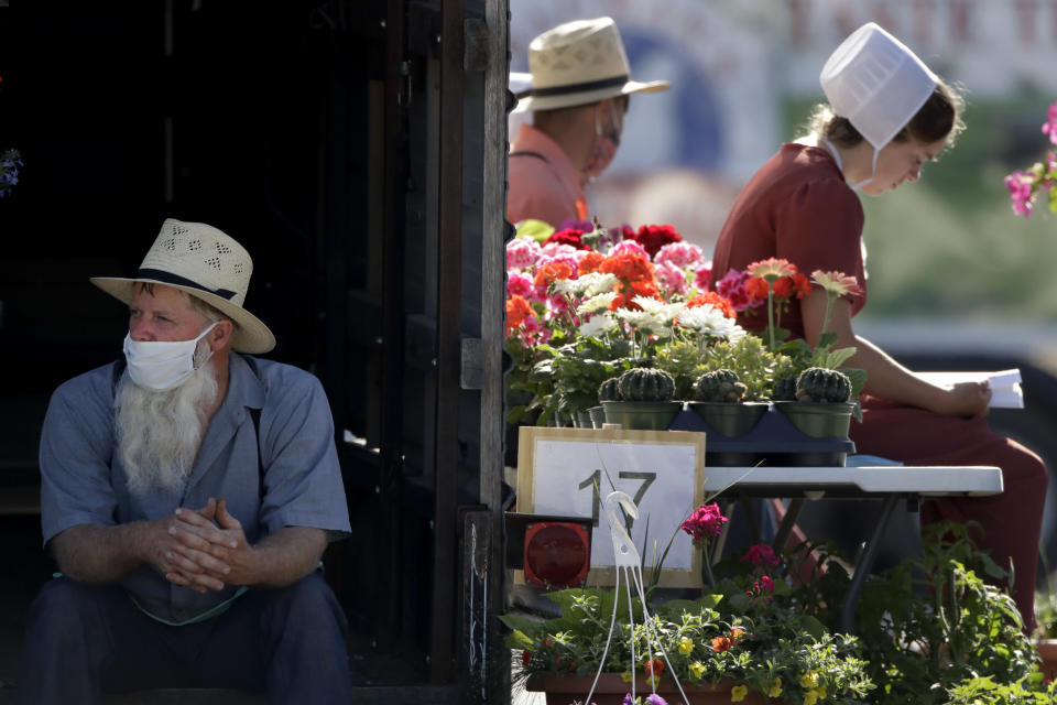 Vendors wait for customers at a drive-thru farmers market Saturday, May 2, 2020, in Overland Park, Kan. The market has moved from its usual home to a sprawling parking lot allowing for people to spread out and shop from their cars as a measure to stem the spread of COVID-19. (AP Photo/Charlie Riedel)