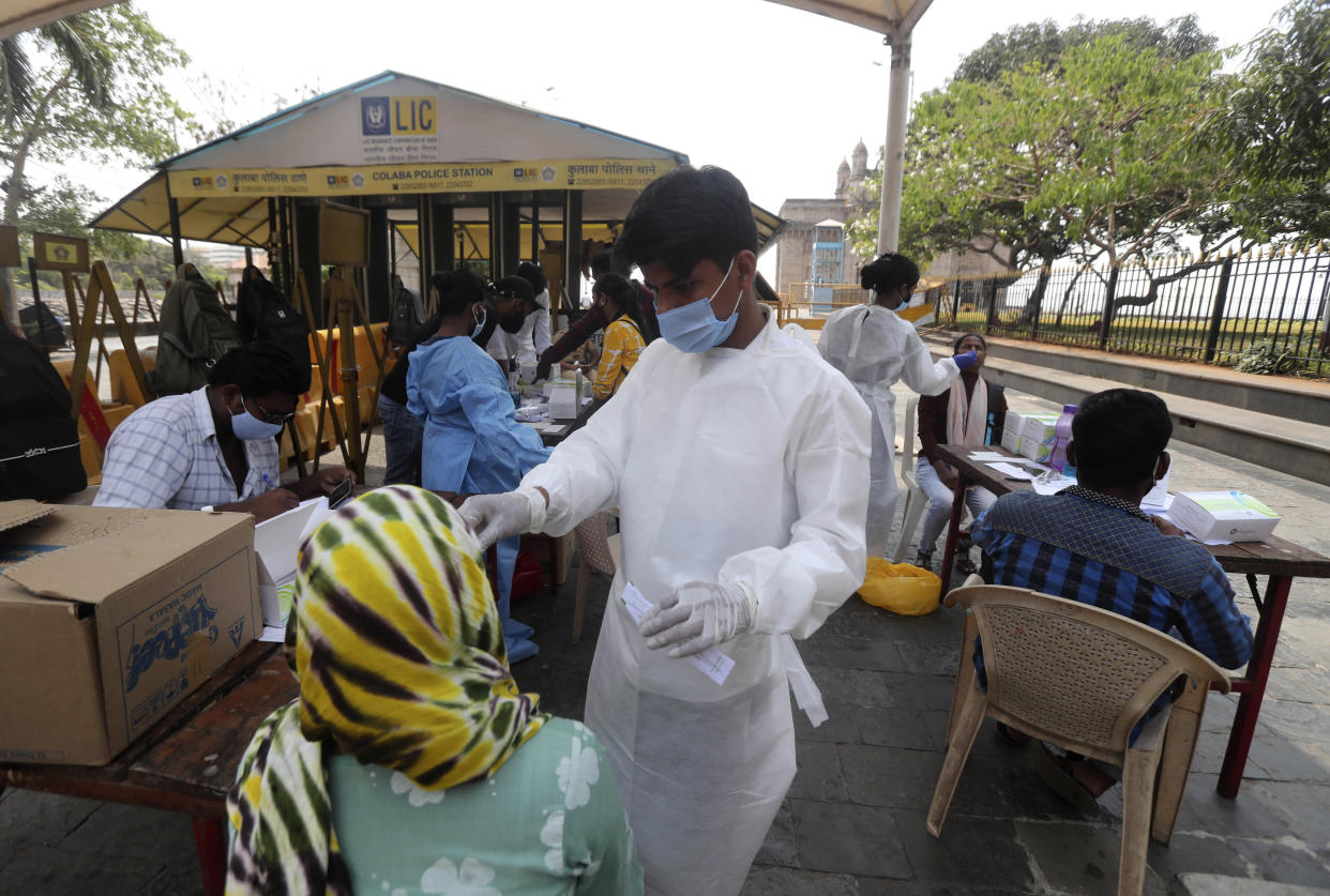 A health worker takes a nasal swab sample of a woman to test for COVID-19 near the landmark Gateway of India in Mumbai, India, Monday, April 5, 2021. India reported its biggest single-day spike in confirmed coronavirus cases since the pandemic began Monday, and officials in the hard-hit state home to Mumbai are returning to the closure of some businesses and places of worship in a bid to slow the spread. (AP Photo/Rafiq Maqbool)