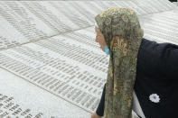 Djulija Jusic who lost her two sons and the 33 relatives in Srebrenica massacre looks at names at the memorial cemetery in Potocari near Srebrenica, Bosnia, Friday, May 28, 2021. U.N. judges on Tuesday, June 8 deliver their final ruling on the conviction of former Bosnian Serb army chief Radko Mladic on charges of genocide, war crimes and crimes against humanity during Bosnia's 1992-95 ethnic carnage. Nearly three decades after the end of Europe's worst conflict since World War II that killed more than 100,000 people, a U.N. court is set to close the case of the Bosnian War's most notorious figure. (AP Photo/Eldar Emric)
