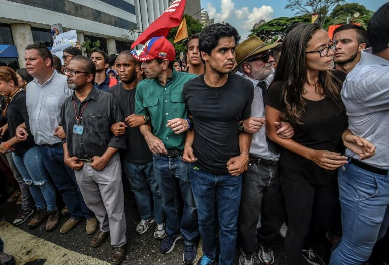 Venezuelan opposition leader Henrique Capriles (C) takes part in a march paying homage to student Juan Pablo Pernalete, killed a day before when he was hit by a gas grenade during a protest against President Maduro, in Caracas, on April 27, 2017