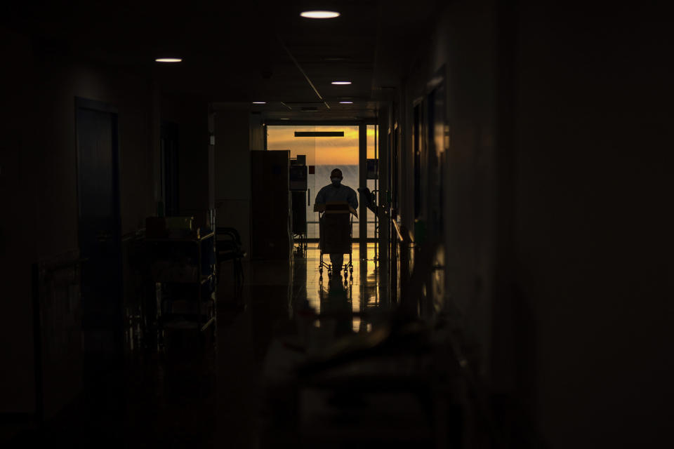 A nursing assistant who works with nurse Marta Fernandez works at the COVID-19 ward at the hospital del Mar in Barcelona, Spain, Wednesday, Nov. 18, 2020. (AP Photo/Emilio Morenatti)