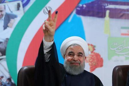 FILE PHOTO: Iran's President Hassan Rouhani gestures as he registers to run for a second four-year term in the May election, in Tehran, Iran