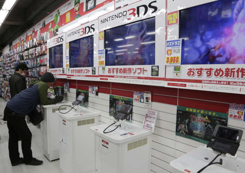 In this photo taken Monday, Dec. 16, 2013, a shopper try out Nintendo 3DS at an electronics store in Tokyo. This holiday season Nintendo faces a critical test with its Wii U video game console that is pitted against Sony's PlayStation 4 and Microsoft's Xbox One as it seeks to revive flagging sales. (AP Photo/Shizuo Kambayashi)