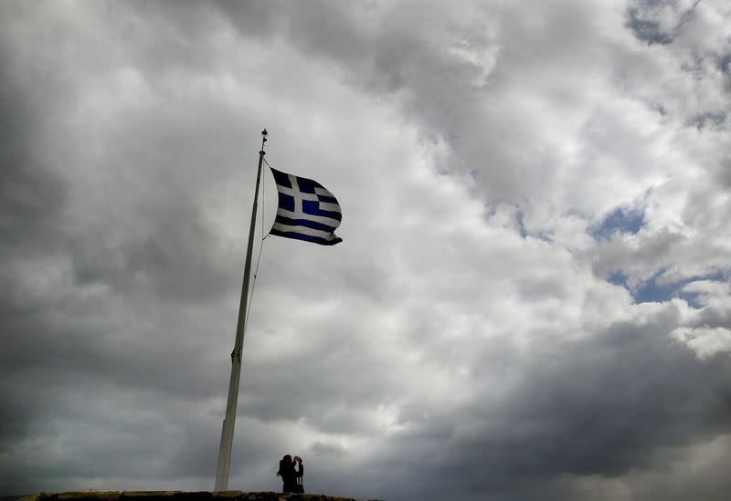 A tourist takes photos under a Greek flag atop the Acropolis hill in Athens