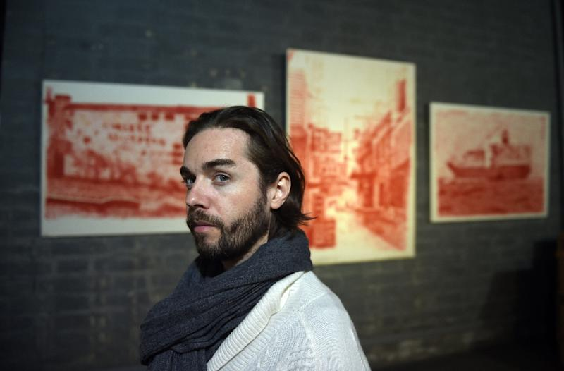 French artist Alexandre Ouairy poses in front of his paintings ahead of an exhibtion at the Red Gate Gallery in Beijing