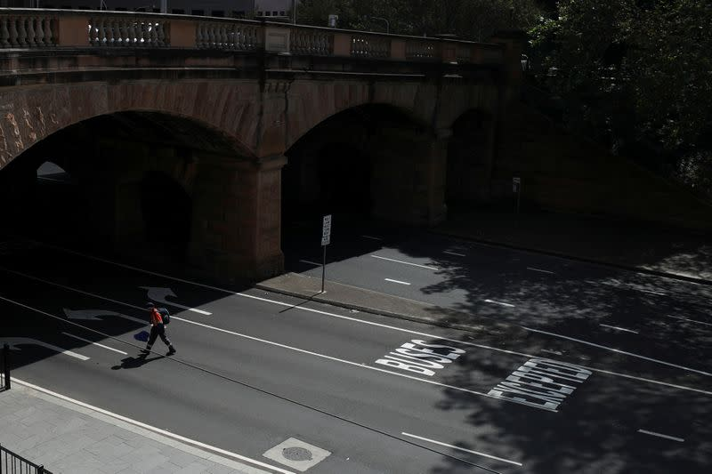 A man crosses an almost empty street during a workday following the implementation of stricter social-distancing and self-isolation rules to limit the spread of the coronavirus disease (COVID-19) in Sydney