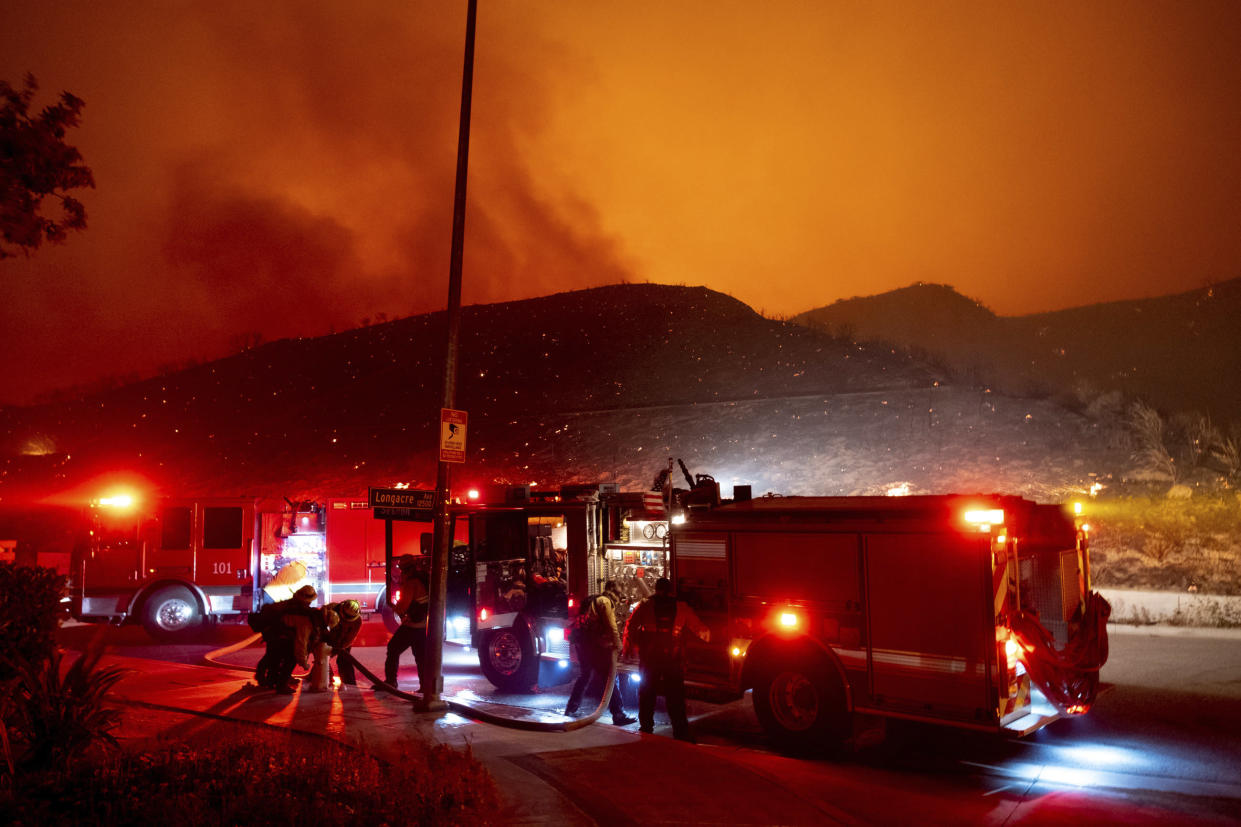 Firefighters refill their truck with water along Sesnon Boulevard early Friday morning, Oct. 11, 2019, as flames burn on the hills in Granada Hills, Calif. (Photo: David Crane/The Orange County Register via AP)