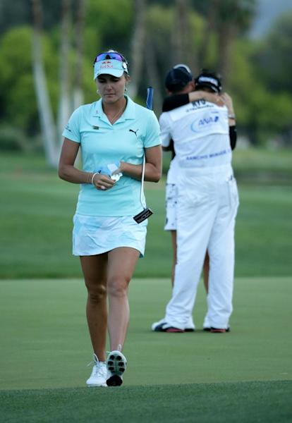 Lexi Thompson of the US walks off the 18th green as Ryu So-Yeon of South Korea celebrates with her caddie after Ryu defeated Thompson in a playoff during the final round of the ANA Inspiration, in Rancho Mirage, California, on April 2, 2017