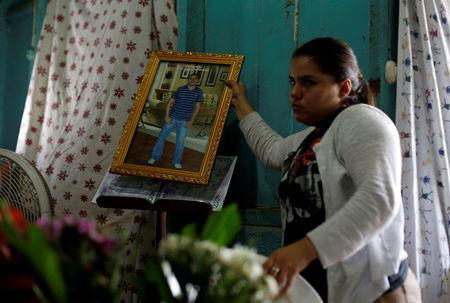A relative holds a picture of Darwin Manuel Urbina, 29, who according to nation's Red Cross was shot dead during a protest over a controversial reform to the pension plans of the Nicaraguan Social Security Institute (INSS), during his funeral in his home in Managua, Nicaragua April 21, 2018. REUTERS/Jorge Cabrera