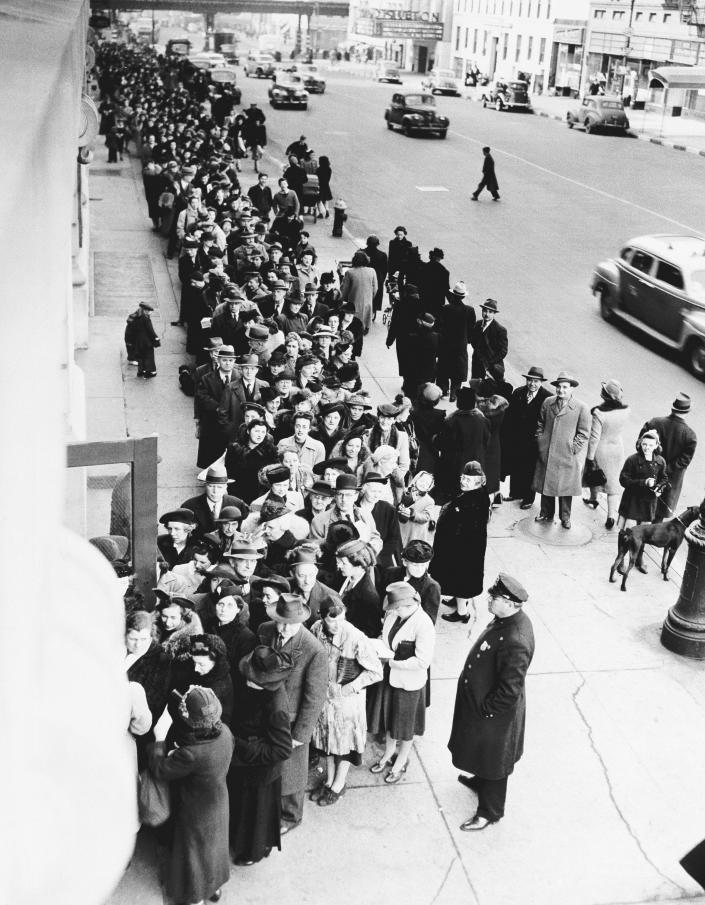 FILE - In this Feb. 23, 1943, file photo New Yorkers stand on long lines outside of schools all over the city to get their War Ration Book No. 2, during World War II. Not since World War II when people carried Ration Books with stamps that allowed them to purchase meat, sugar, butter, cooking oil and gasoline has the entire nation been asked to truly sacrifice for a greater good. (AP Photo, File)