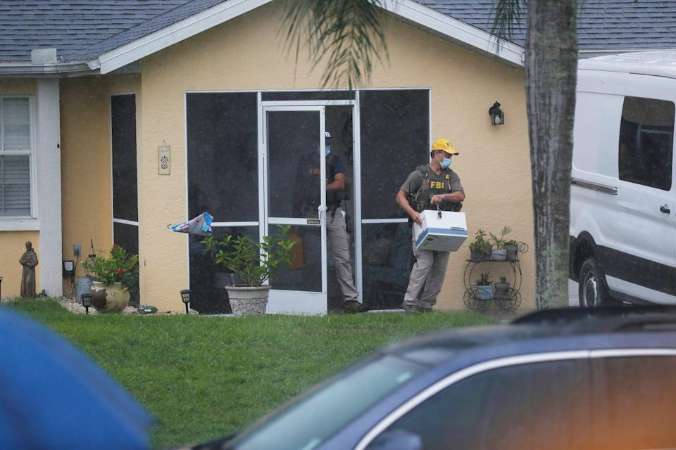An FBI agent walks out of the door of the house with a box