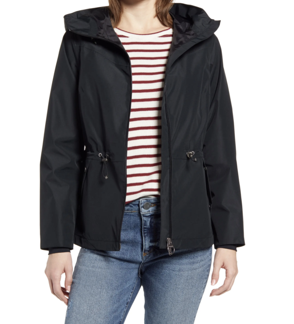 model wearing black barbour rain jacket, red and white striped shirt, and jeans