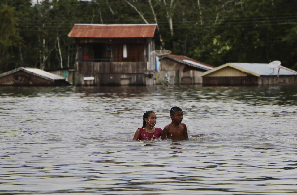 Residents move through on a flooded street in Anama, Amazonas state, Brazil, Thursday, May 13, 2021. (AP Photo/Edmar Barros)