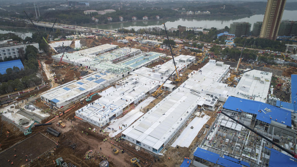 This Saturday, Feb. 1, 2020, photo released by China's Xinhua News Agency, shows construction workers at the site of the Huoshenshan temporary field hospital being built in Wuhan in central China's Hubei Province. China's death toll from a new virus has increased to 304 with more than 14,000 cases, amid warnings from the World Health Organization that other countries need to be prepared in the event the disease spreads among their populations. (Xiao Yijiu/Xinhua via AP)
