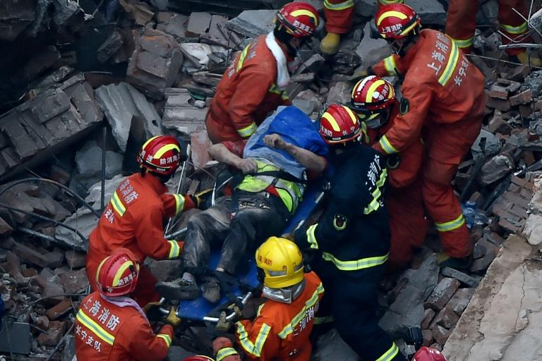 About half of the low-rise building collapsed in Shanghai, crushing construction workers under piles of toppled concrete pillars and shattered wooden beams