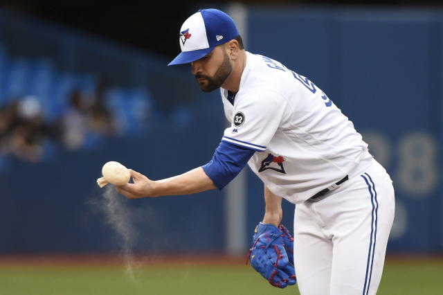 Toronto Blue Jays starting pitcher Jaime Garcia picks up the rosin bag after loading the bases with Atlanta Braves during the second inning of a baseball game Tuesday, June 19, 2018, in Toronto. (Nathan Denette/The Canadian Press via AP)