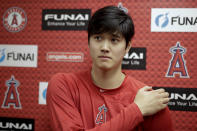 FILE - In this Feb. 13, 2019, file photo, Los Angeles Angels' Shohei Ohtani, recovering from Tommy John surgery, talks to the media at their spring baseball training facility in Tempe, Ariz. Shohei Ohtani, Yu Darvish and Daisuke Matsuzaka are all examples of pitchers who have suffered significant arm injuries relatively early in their major league careers after arriving from Japan. Whether he wants to be or not, Yusei Kikuchis rookie season is a science experiment. An attempt to see whether pitchers brought from Asia to Major League Baseball should be handled differently in their first season. (AP Photo/Chris Carlson, File)