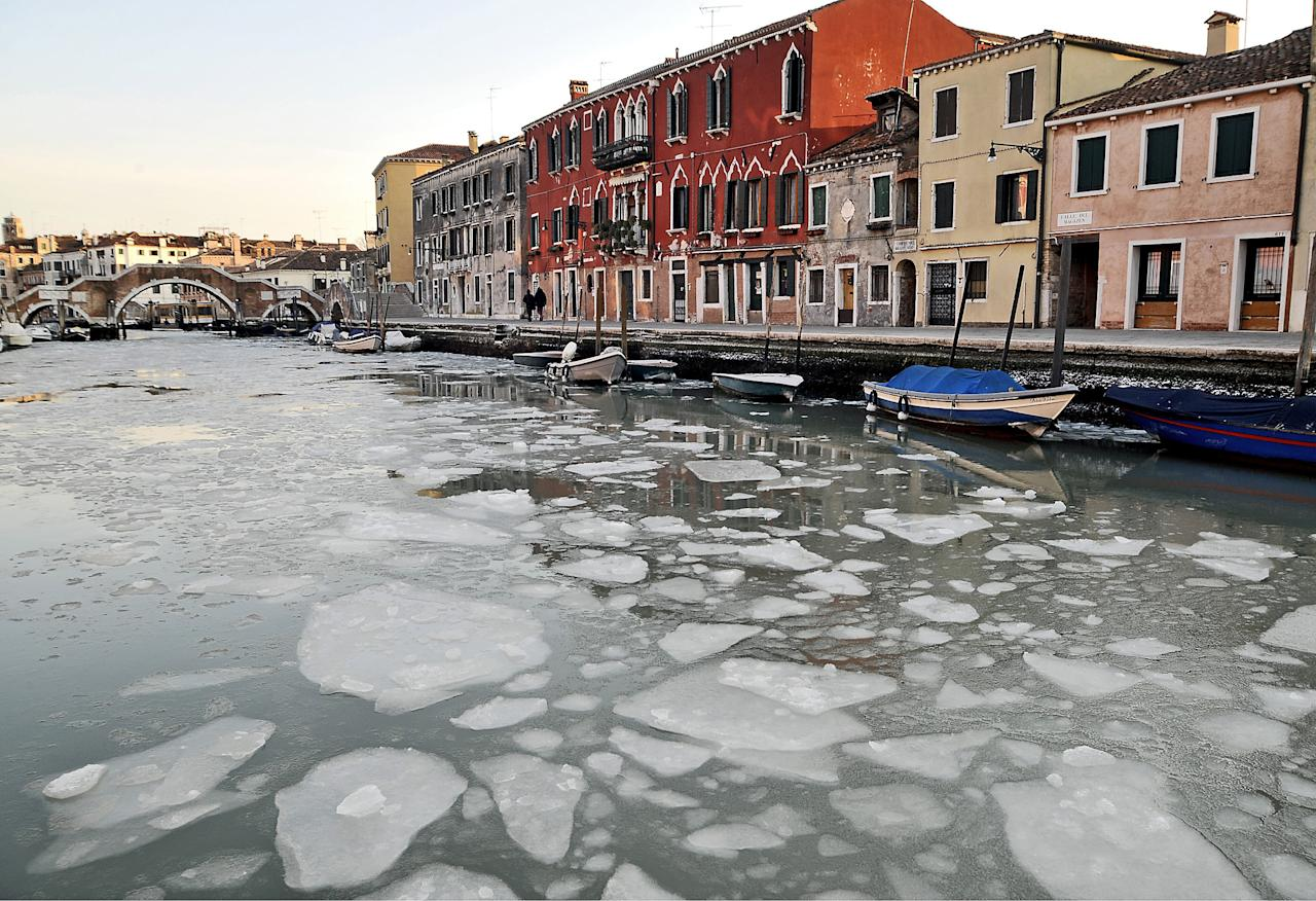 A view of the Cannaregio channel, partially iced because of unusually low temperatures, in Venice, Italy, Monday, Feb. 6, 2012. Schools will be closed in Rome on Tuesday, as Italy copes with unusually heavy snow for the Mediterranean country. So far, ten deaths have been linked to winter weather, including two people who were crushed under a collapsed roof south of Rome, and a 91-year-old woman in the northeast port of Trieste who was knocked down by strong winds. In the north, rescuers had to pluck people from their homes, as piles of snow reached 3 meters (10 feet) in some areas. In Milan, Italy's fashion and financial capital, temperatures fell to minus 12 Celsius (10 Fahrenheit) on Monday, and the authorities opened a section of the city subway to shelter some 100 homeless people. (AP Photo/Luigi Costantini)