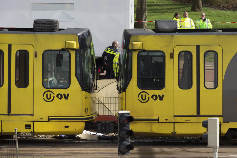 The body of one of three victims is covered with a white sheet as it lies next to a tram after a shooting incident in Utrecht, Netherlands, Monday, March 18, 2019. A gunman killed three people and wounded nine others on a tram in the central Dutch city of Utrecht, sparking a manhunt that saw heavily armed officers with sniffer dogs zero in on an apartment building close to the shooting. (AP Photo/Peter Dejong)