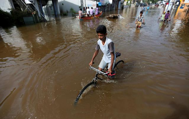 <p>A boy rides his bike along a flooded road in Nagoda village, in Kalutara, Sri Lanka, May 29, 2017. (Dinuka Liyanawatte/Reuters) </p>
