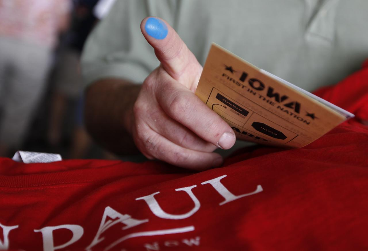 A voter who voted for Republican presidential candidate Rep. Ron Paul, R-Texas, shows his finger marked with indelible ink as he picks up a free shirt at the Republican Party's Straw Poll in Ames, Iowa, Saturday, Aug. 13, 2011. (AP Photo/Charles Dharapak)