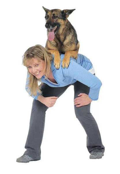 "This undated image provided by Trina Kaye shows Babette Haggerty, the author of ""The Best Dog Tricks on the Planet,"" with a German shepherd named Steve sitting on her back. Haggerty, veteran dog trainer to the stars, has packed 106 teach-them-yourself stunts into her new book, ""The Best Dog Tricks on the Planet."" (AP Photo/Trina Kaye)"