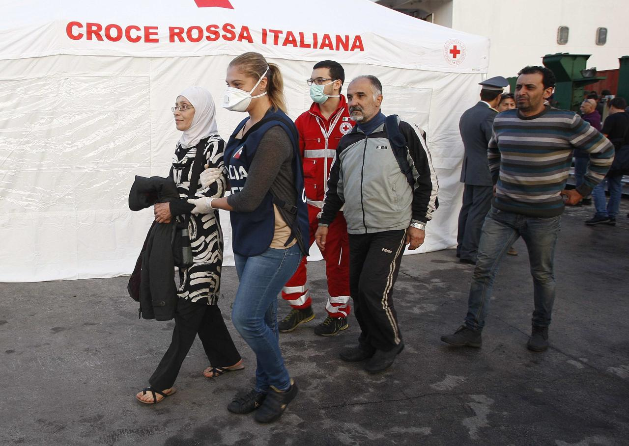 Migrants are helped as they arrive by a rescue boat with a group that includes Syrian and Palestinian refugees at Catania harbour in the island of Sicily October 8, 2013. REUTERS/Antonio Parrinello (ITALY - Tags: SOCIETY IMMIGRATION)