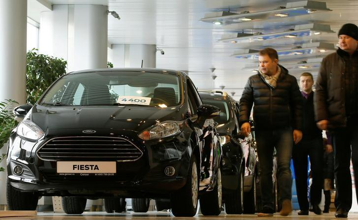 FILE PHOTO: Visitors walk past Ford cars at a dealership in Moscow