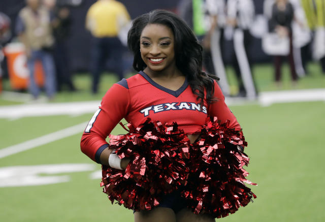 Honorary cheerleader Simone Biles stands on the field before the Houston Texans and San Francisco 49ers game. (AP)