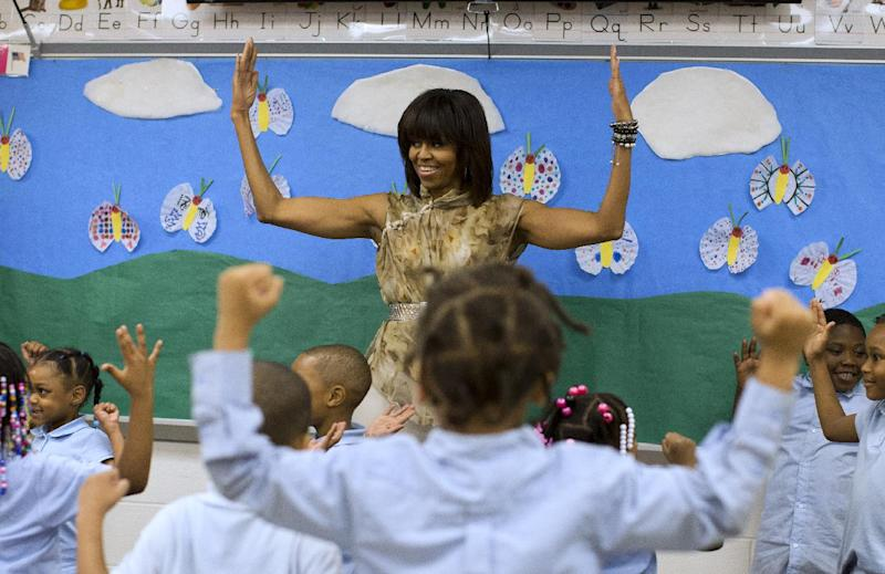 First lady Michelle Obama dances with a pre-K class at Savoy Elementary School in Washington, Friday, May 24, 2013. The Savoy School was one of eight schools selected last year for the Turnaround Arts Initiative at the President's Committee on the Arts and Humanities.  Turnaround Arts Schools use the arts as a central part of their reform strategy to improve low performing schools  (AP Photo/Evan Vucci)