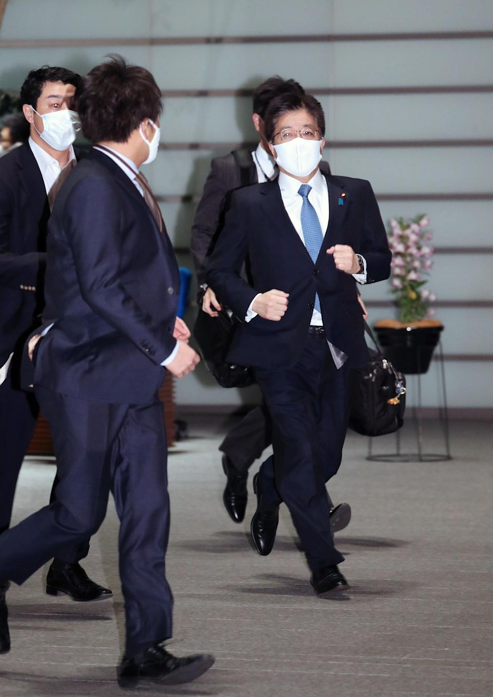 Japanese Chief Cabinet Secretary Katsunobu Kato (R) rushes into the prime minister official residence after a strong earthquake hit northeastern JapanEPA