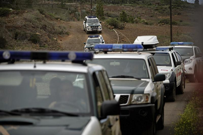 Members of the Spanish Civil Guard patrol make their way to the crime scene (AP)
