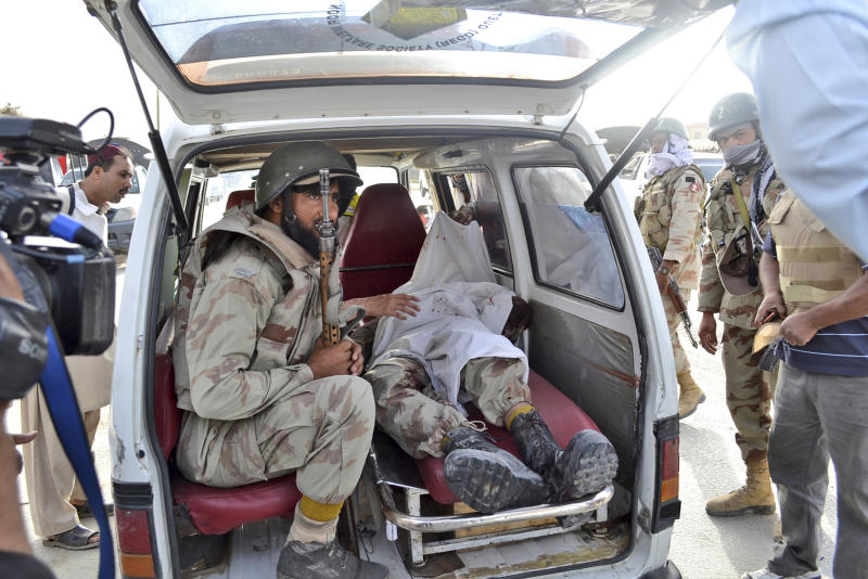 A Pakistani paramilitary soldier sits in the back of a vehicle next to the lifeless body of his colleague who was killed by gunmen during a gun battle at a hospital, in Quetta, Pakistan, Saturday, June 15, 2013. Gunmen took over parts of a hospital in southwestern Pakistan Saturday after a bomb went off inside its emergency room, officials said. Several people died before authorities stormed the building and freed the hostages trapped inside. (AP Photo/Arshad Butt)