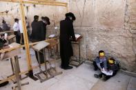 Ultra-Orthodox Jewish boys play as men pray in front of the Western Wall, Judaism's holiest prayer site, in Jerusalem's Old City