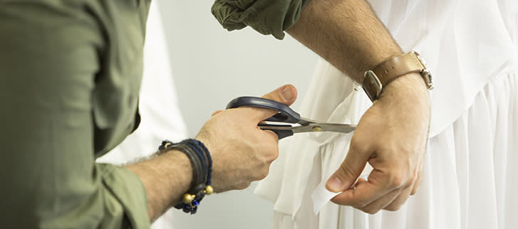 Closeup of a man cutting white fabric with a pair of scissors.