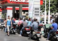 Motorbike riders wait to get fuel at a gas station in Beirut