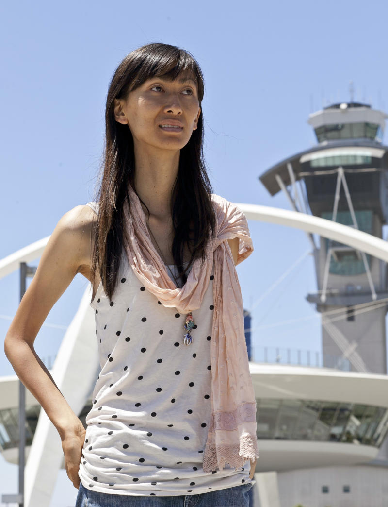 Ashley Yang, a transgender woman poses for a photo at Los Angeles International Airport, (LAX) on Thursday, Aug. 4, 2011, in Los Angeles. Yang was fired from her Transportation Security Administration,  passenger screener job at LAX for using the women's room. She recently received a five-figure settlement, back pay and mandatory transgender sensitivity for TSA managers at the LAX airport. (AP Photo/Damian Dovarganes)