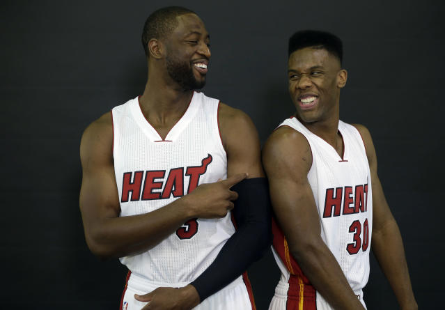 Miami Heat guards Dwyane Wade, left, and Norris Cole, right, joke as they poses for portraits during NBA basketball media day, Friday, Sept. 26, 2014, in Miami. (AP Photo/Lynne Sladky)