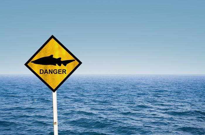 Open water with a sign that has a picture of a shark and danger written on it.