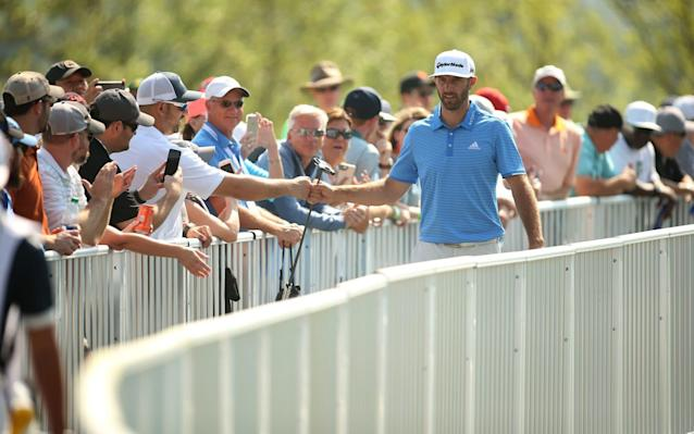 <span>Dustin Johnson shakes the hand of a fan during his final round</span>