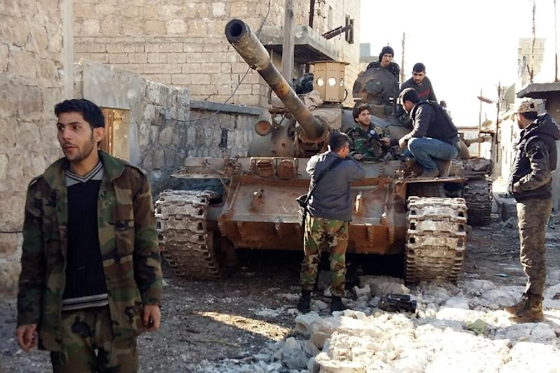 Government forces chat near a tank three kilometres from the Shiite villages of Nabbul and Zahra in Syria's northern Aleppo province on February 2, 2016 (AFP Photo/George Ourfalian)