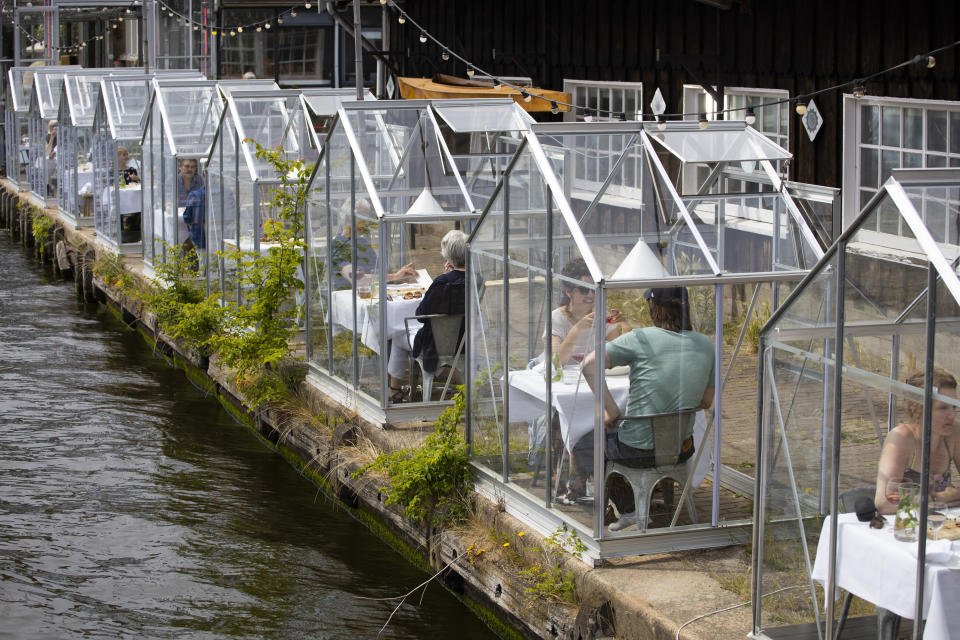 FILE - In this Monday, June 1, 2020 file photo, customers seated in small glasshouses enjoy lunch at the Mediamatic restaurant in Amsterdam, Netherlands. The coronavirus pandemic is gathering strength again in Europe and, with winter coming, its restaurant industry is struggling. The spring lockdowns were already devastating for many, and now a new set restrictions is dealing a second blow. Some governments have ordered restaurants closed; others have imposed restrictions curtailing how they operate. (AP Photo/Peter Dejong, File)