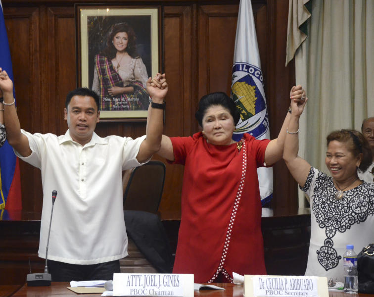 Flamboyant former Philippine First Lady Imelda Marcos is proclaimed the winning congresswoman of the province of Ilocos Norte, the home province of her late husband Ferdinand Marcos, following her landslide win in the country's midterm elections Tuesday May 14, 2013 in Laoag, Ilocos Norte in northern Philippines. More than 50 million Filipinos trooped to polling centers to elect senators, congressmen and down to municipal mayors for the country's midterm elections. Raising her hands are Provincial Board of Canvassers' Joel Gines, left, and Cecilia Aribuabo. (AP Photo)