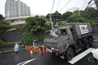 A Japan Self Defense Force member drives its vehicle for rescue work though a police road block near a mudslide area following heavy rains at the Izusan district in Atami, Shizuoka Prefecture, west of Tokyo, Sunday, July 4, 2021. The mudslide carrying a deluge of black water and debris crashed into rows of houses in the town following heavy rains on Saturday, leaving multiple people missing, officials said. (AP Photo/Eugene Hoshiko)