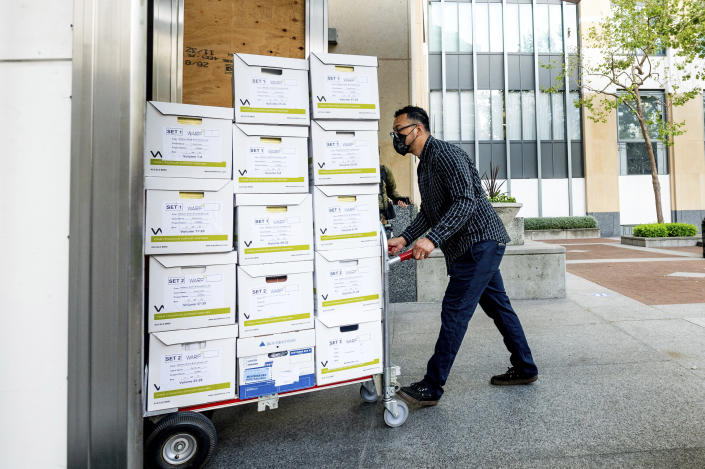 A member of Apple's legal team rolls exhibit boxes into the Ronald V. Dellums building in Oakland, Calif., as the company faces off in federal court against Epic Games on Monday, May 3, 2021. Epic, maker of the video game Fortnite, charges that Apple has transformed its App Store into an illegal monopoly. (AP Photo/Noah Berger)