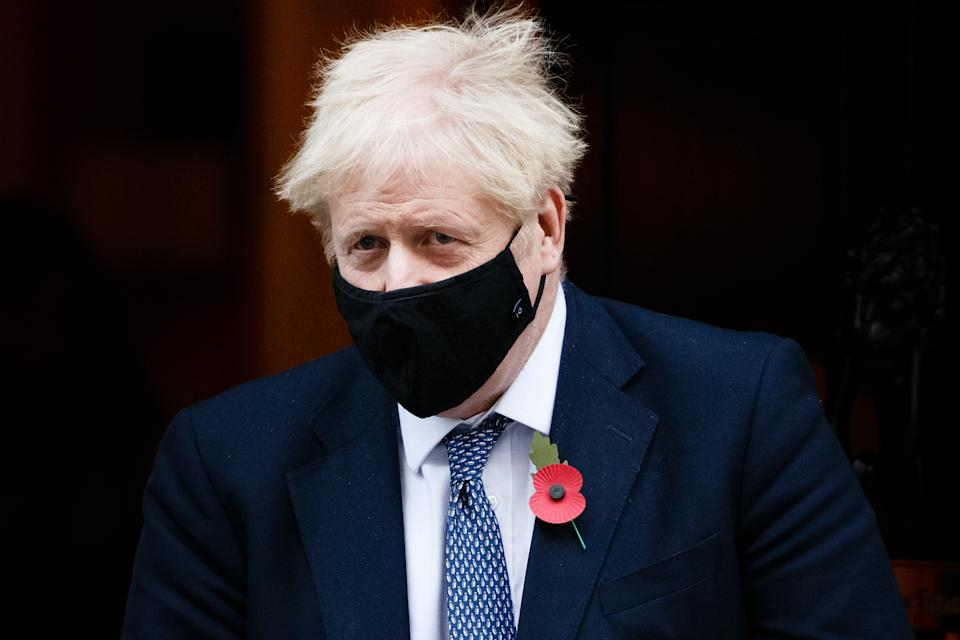 British Prime Minister Boris Johnson wears a face mask and remembrance poppy as he leaves 10 Downing Street heading for his weekly Prime Minister's Questions (PMQs) appearance in the House of Commons in London, England, on November 4, 2020. MPs will vote later today in Parliament on whether to approve the government's plans for a four-week coronavirus lockdown for England, due to begin tonight at midnight, ordered by Johnson on Saturday citing fears that covid-19 again threatens to overwhelm the National Health Service (NHS). (Photo by David Cliff/NurPhoto via Getty Images)