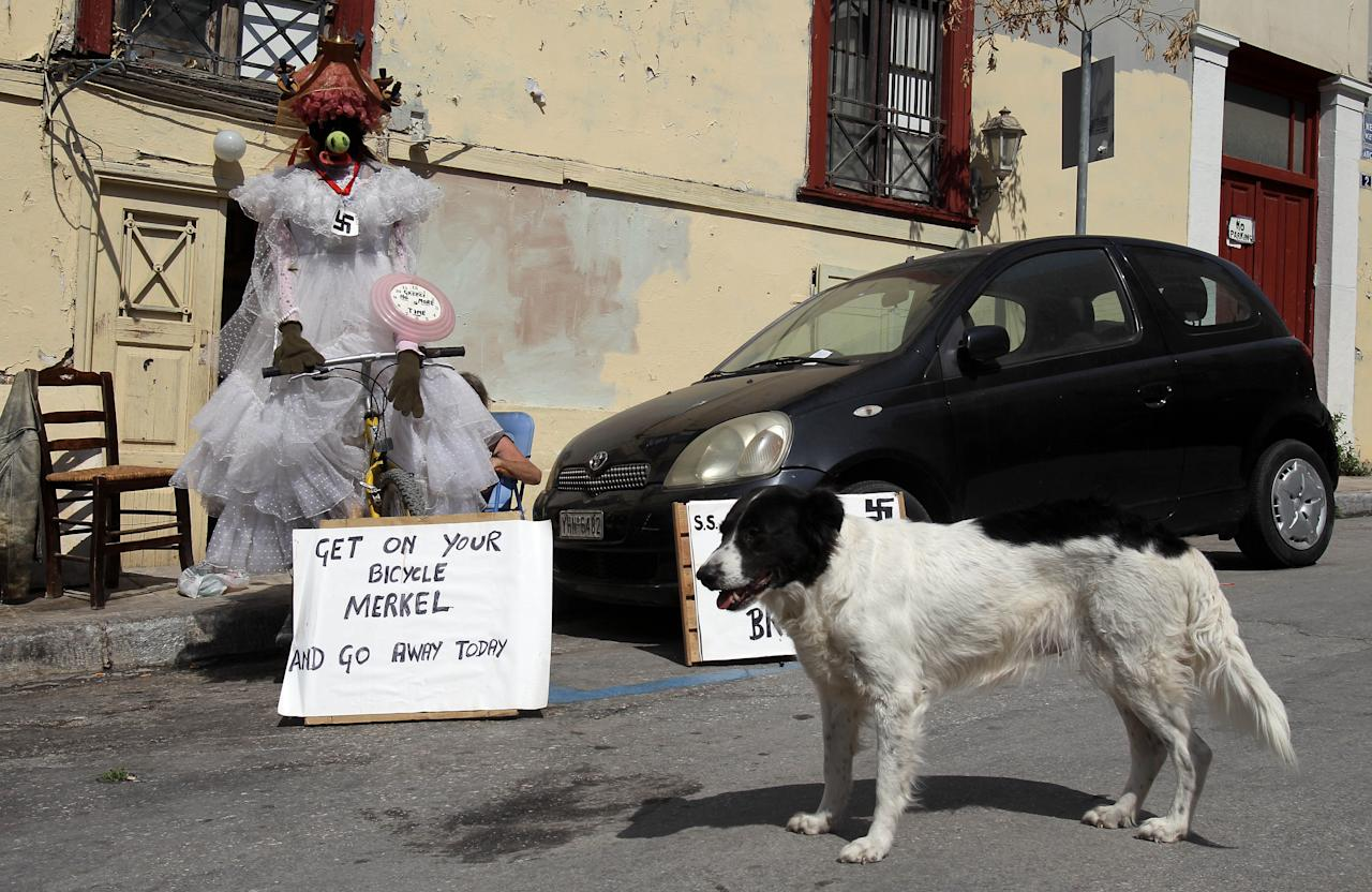 "A dog stops in front of a wedding dress-clad mannequin on a bicycle next to a hand-written poster reading ""Get on your bicycle Merkel and go away today"", as part of a street installation in Athens, Tuesday, March 20, 2012. Greece's Parliament is set to approve the debt-crippled country's new international bailout deal late Tuesday as Communist party supporters prepare to protest against the austerity measures being imposed in return for the rescue funds. The euro 172 billion ($226 billion) rescue package has already been approved at committee level. (AP Photo/Thanassis Stavrakis)"